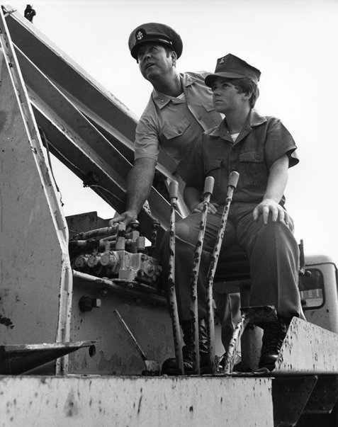 Constructionman Camella J. Jones learns how to operate a large crane from a Chief Petty Officer. She was the first woman of the Navy to qualify as a Heavy Equipment Operator and to be assigned to a U.S. Navy Construction Battalion, November 1972. Photograph by PH3 Paul Mansfield, USN. NHHC Photograph Collection, NH 106746.