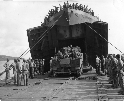 """Seabee's have """"married"""" a pontoon causeway to an LST to offload the ship's cargo to shore. 1944 [U.S. Navy Seabee Musem]"""