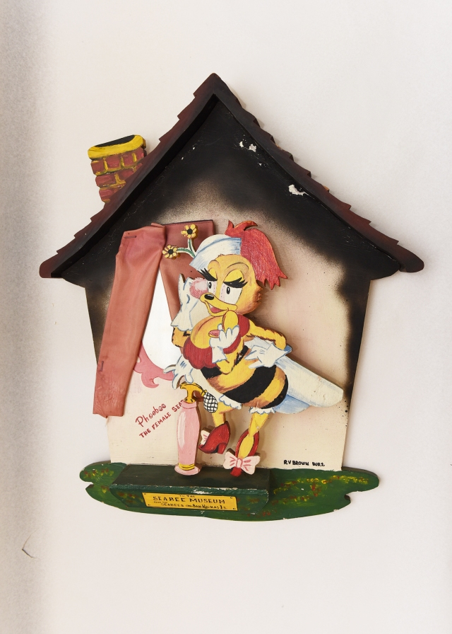 Wooden shadowbox of Phoebe standing in front of house, donated to the Seabee Museum from the Seabees on San Nicholas Island. (U.S. Navy Museum Collection)