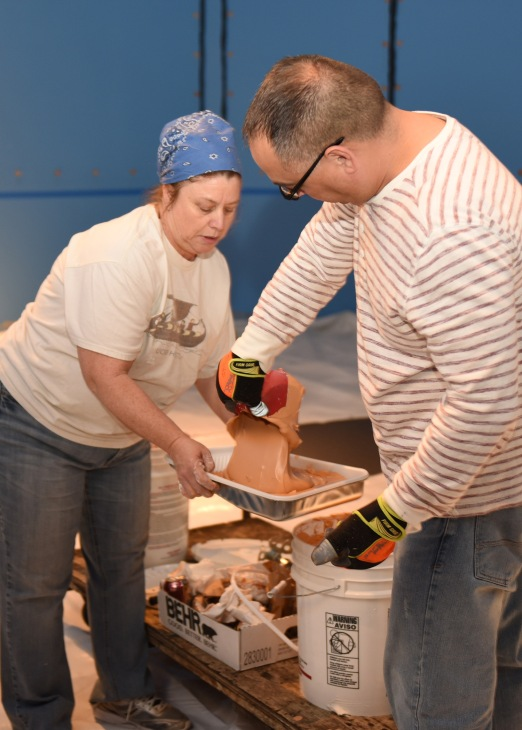 Museum Curator Kim Crowell and Exhibit Specialist Tim Morales, mix the paint to apply to the walls during installation phase.