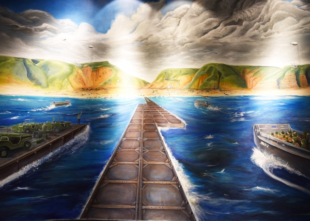 A mural that depicts the landing at Normandy. At center is a pontoon causeway in which their transport, usage, placement and maintenance was under the charge of the Seabees.