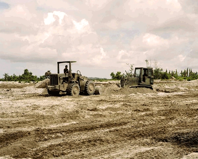 Seabees assigned to NMCB 4 are using a bulldozer and front loader to remove wet ash from Subic Bay and Cubi Point. (U.S. Navy Seabee Museum)