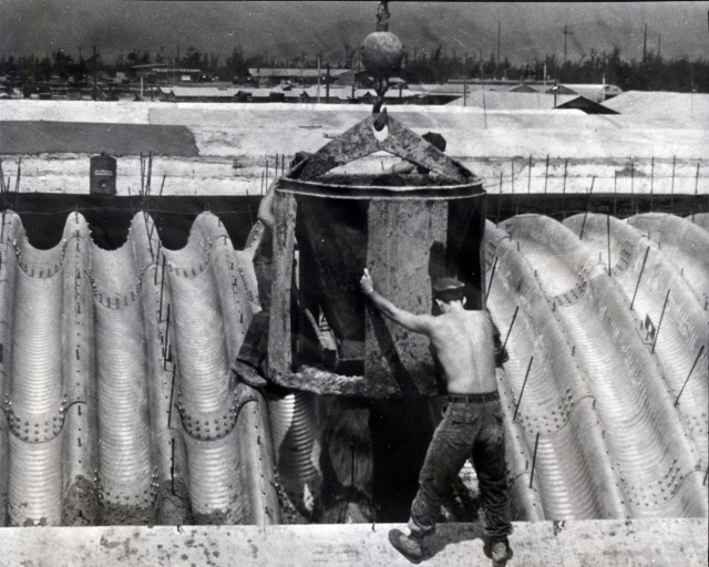 Seabees with NMCB-121 pour concrete to form a protective cover for a Wonder Arch aircraft shelter for Marine Aircraft Group 16, located in Military Region I, Republic of Vietnam.