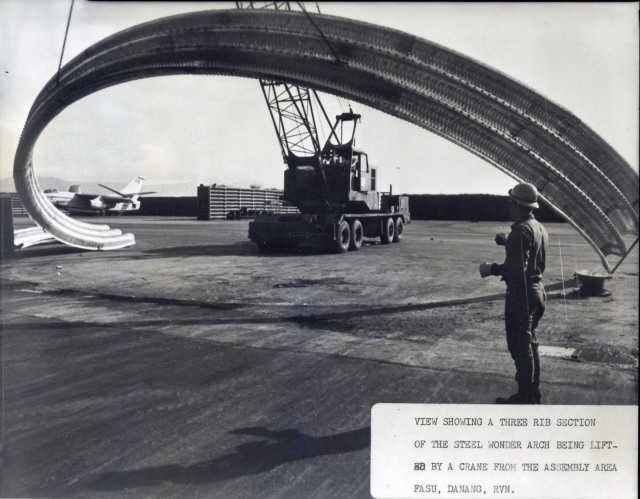 "A 3-rib section of a steel ""Wonder Arch"" aircraft shelter is being lifter into position on a parking apron at the DaNang Air Base. Seabees are from NMCB-3."
