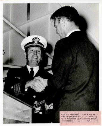 Captain Merdinger accepting key to new hangar from Mr. C.J. Mark , Vice President, Continental Heller Corporation. Note, description is scratched out with pen so information may not be correct.