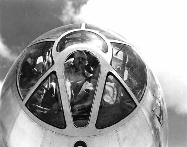 Combs peers through the nose of a Boeing B-29 Superfortress, North Field, Tinian, Feb. 27, 1945.