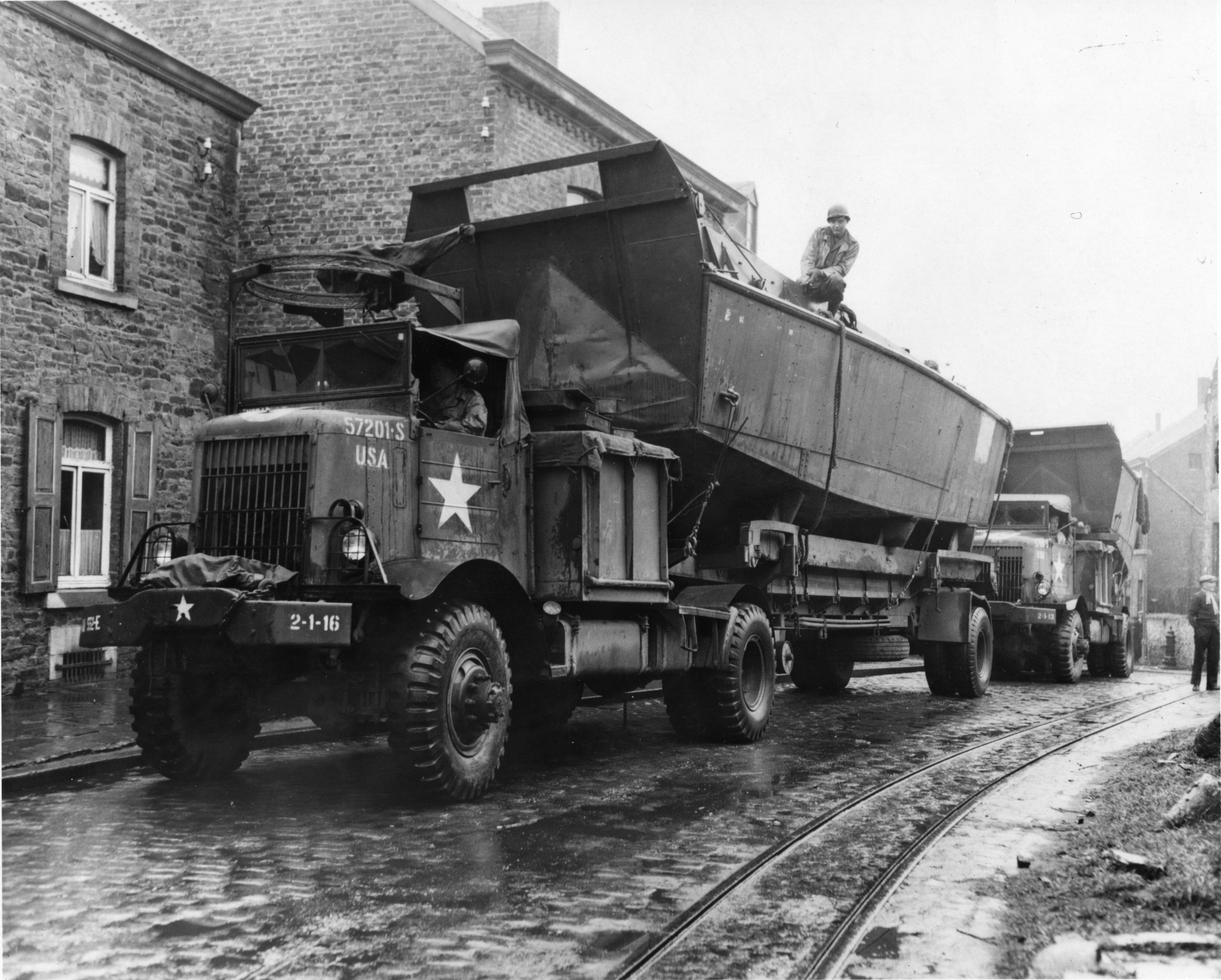 Landing craft are loaded onto flatbed trucks for transporting ov